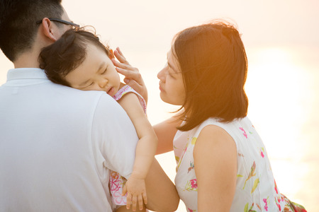 Portrait of lovely Asian family seated on beach outdoor vacation, during summer sunset, natural sunlight with flare. photo