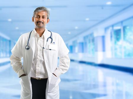 Indian doctor. Mature Indian male medical doctor standing inside hospital. Handsome Indian model portrait.