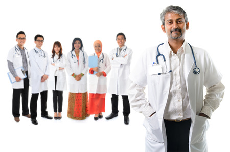 Multiracial diversity Asian medical team, expertise senior and mature doctors leading young practitioners, standing isolated on white background. Stock Photo