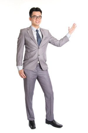 Full length picture of a young business man presenting something in the back with one hand in his pocket while looking at the camera with a smile on his face, isolated on white background. photo
