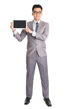 Full body Asian businessman hand holding digital computer tablet, standing isolated on white background. photo