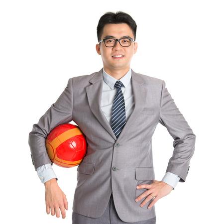jugando futbol: Retrato de hombre de negocios asiático con el balón de fútbol de pie aislado en fondo blanco.