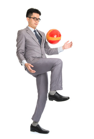 Portrait of full length Asian businessman playing with soccer ball, isolated on white background. photo