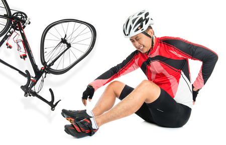 sports injury: Asian biker fell down from bike, injured at back with painful facial expression, sitting on floor, isolated on white background.