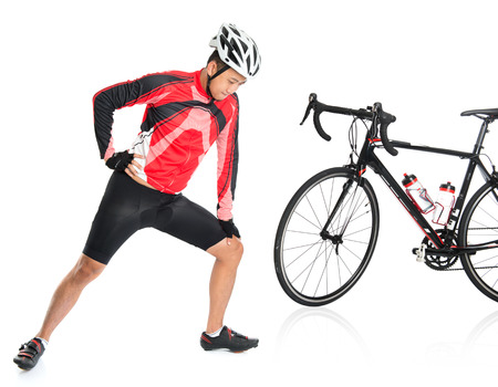 Asian biker warming up or cool down, standing beside bike, isolated on white background.