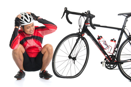 puncture: Asian cyclist headache and looking at his flat tire bike, isolated on white background.