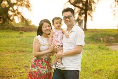 Happy Asian family portrait. Outdoor playing time during summer sunset. photo