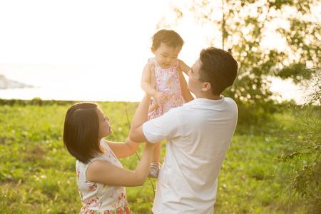 familias jovenes: Familia asi�tica feliz jugando en el prado durante la puesta del sol del verano, al aire libre disparo.