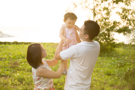 Happy Asian family playing in meadow during summer sunset, outdoors shot. photo