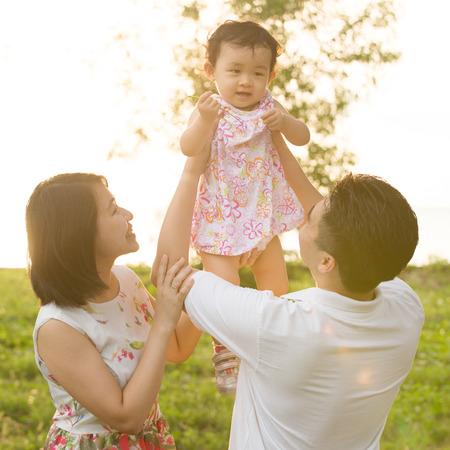 Portrét šťastné asijské rodina hrát spolu na venkovní parku během letní západ slunce.