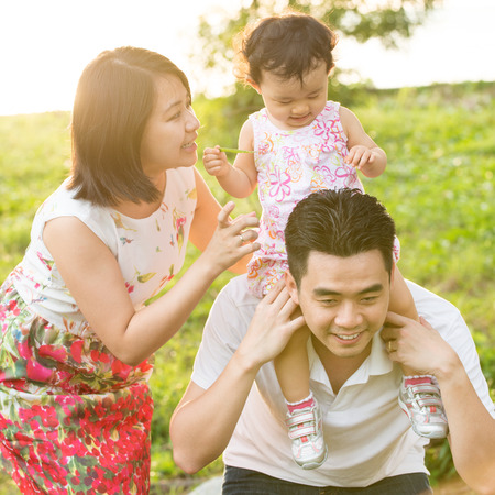 play time: Portrait of happy Asian family playing piggyback at outdoor park during summer sunset. Stock Photo