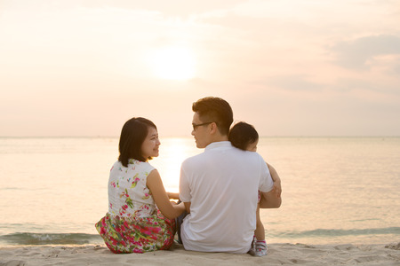 Portrait of young Asian family seated on beach outdoor vacation, during summer sunset, natural sunlight.