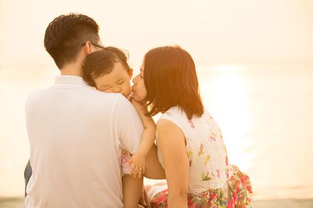 アジアの若い家族の肖像画に着席してビーチの屋外の休暇、夏の日没時にフレアと自然な日光。