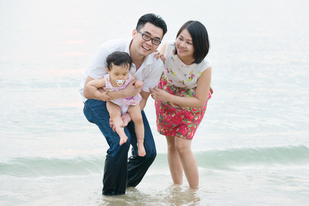 Happy Asian family outdoor on sand beach, vacation during summer, natural sunset sunlight. photo