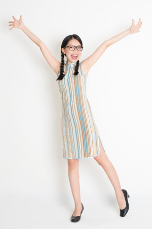 Retrato de longitud completa de Asia niña china brazos extendidos y mirando a la cámara, en cheongsam estilo pasado de moda, de pie en el fondo plano.