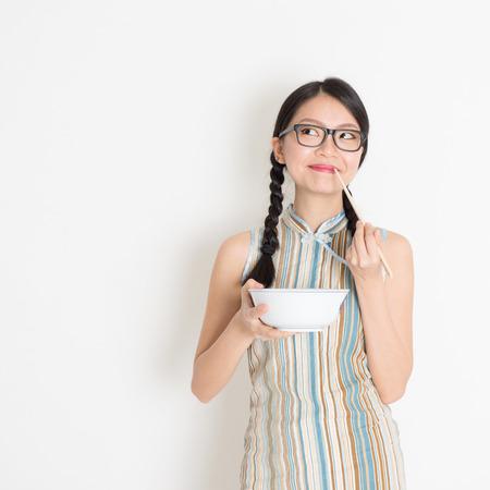 Portrait der asiatischen chinesischen Frau Essen mit Stäbchen, die Reisschüssel, in retro style cheongsam stehend auf einfachen Hintergrund. Standard-Bild - 31478097