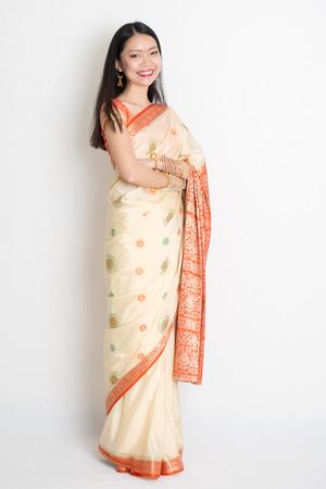 fair skin: Longitud total tono de piel justo conf�a asi�tica femenina india sonriente y de pie en el fondo plano.
