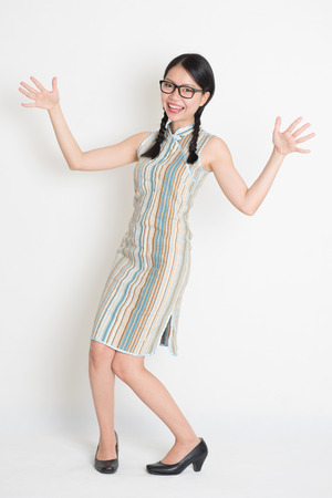 exaggerate: Portrait of full length surprised Asian Chinese female open arms and looking at camera, in retro revival style cheongsam, standing on plain background. Stock Photo