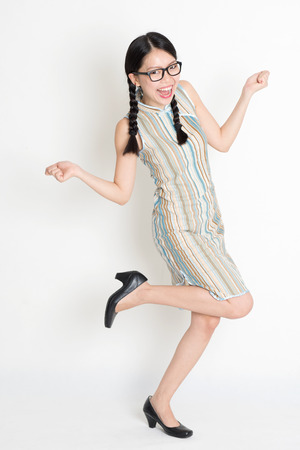 Portrait of excited Asian Chinese female hands holding something looking at camera, in old-fashioned style cheongsam, standing on plain background. photo