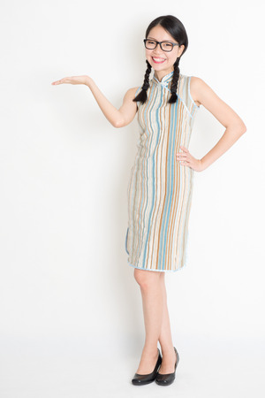 Portrait of full length Asian Chinese girl palm holding something and looking at camera, in old-fashioned style cheongsam, standing on plain background. photo