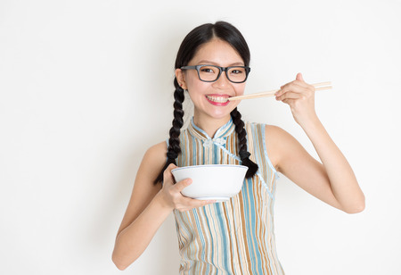 chinese meal: Portrait of Asian Chinese female eating, using chopsticks holding rice bowl, in retro revival style cheongsam standing on plain background. Stock Photo