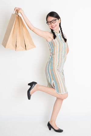 Portrait of excited Asian Chinese woman hands holding paper shopping bags, in retro revival style cheongsam standing on plain background. photo