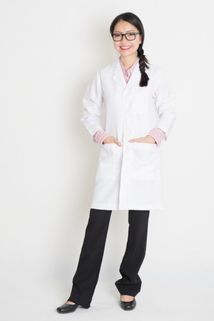 Portrait of Asian Chinese girl in white lab uniform smiling, full body standing on plain background. photo