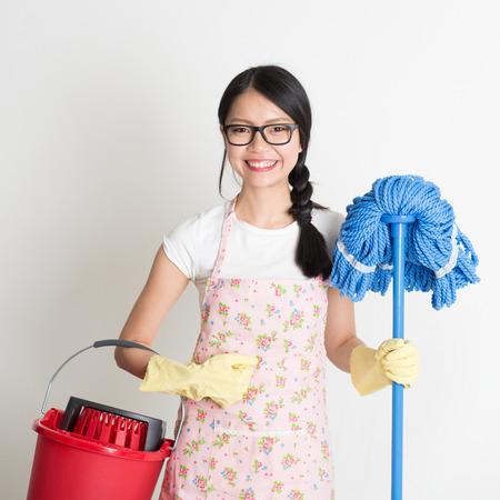 Retrato de la mujer asiática limpieza chino, la celebración de cubo y la fregona en el fondo plano.