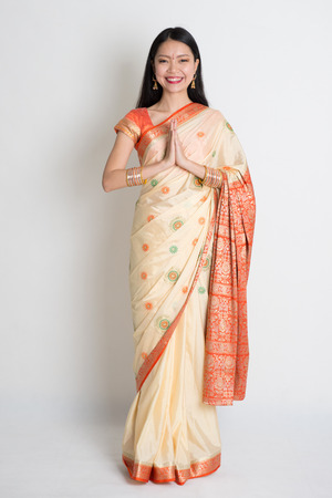indian saree: Asian Indian girl in a greeting pose, traditional sari costume, full length standing on plain background