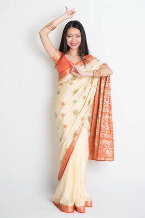 fair woman: Full length Asian Indian female in dancing pose on plain background. Stock Photo