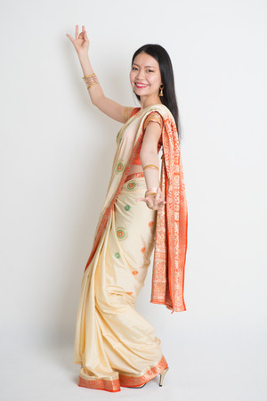 saree: Full length of happy Asian Indian girl dancing on plain background.