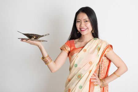 Indian housewife hand holding empty plate ready for food standing on plain background. photo