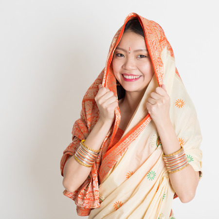 indian fair: Portrait of Indian Muslim girl in sari covered her head, smiling confidently on grey background. Stock Photo