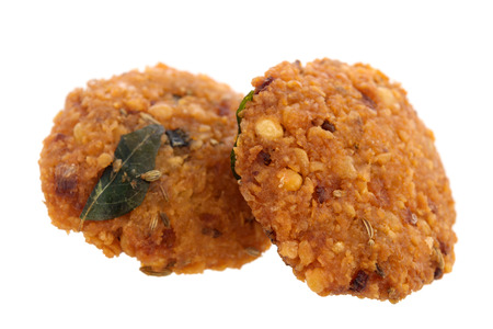 urad dal: Crispy deep fired vadai snack, common street food in the Indian Subcontinent and Sri Lanka, shoot isolated on white background.