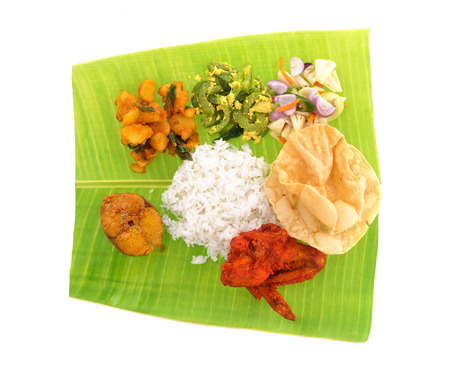 Overhead view of full length Indian banana leaf rice isolated on white background. photo