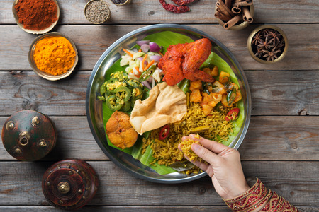 Overhead view of Indian woman's hand eating biryani rice on wooden dining table.