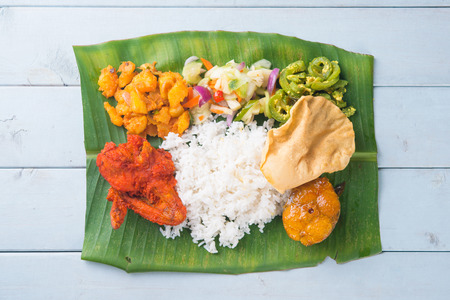 south asians: Indian banana leaf rice, overhead view on wooden dining table. Stock Photo