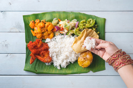 Indian woman eating banana leaf rice, overhead view on wooden dining table. photo