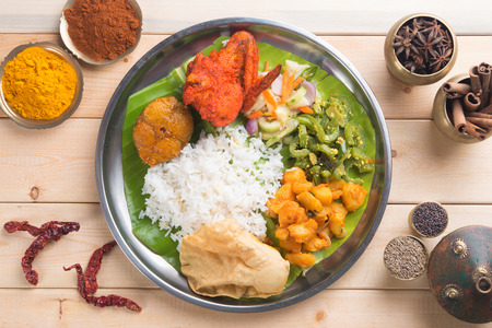 southern indian: Overhead view of Indian mixed rice on wooden dining table with setting. Stock Photo