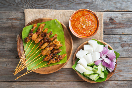 singapore culture: Overhead view Malaysian chicken satay with delicious peanut sauce, ketupat, onion and cucumber on wooden dining table, one of famous local dishes. Stock Photo