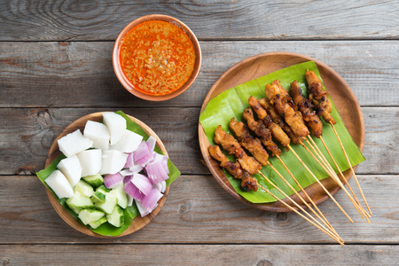 Overhead view Malaysian chicken sate with delicious peanut sauce, ketupat, onion and cucumber on wooden dining table, one of famous local dishes. Stock Photo