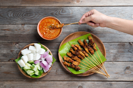 malaysian: Overhead view people holding chicken satay dipping peanut sauce on wooden dining table, one of famous local dishes. Stock Photo