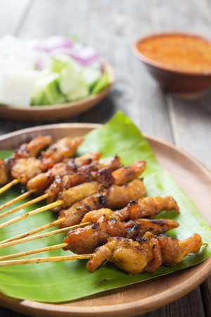 Close up chicken satay on wooden dining table, one of famous local dishes.