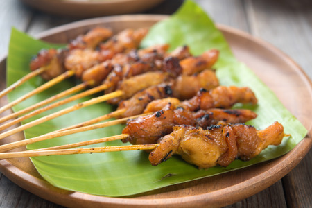 Close up Malaysian chicken satay on wooden dining table, one of famous local dishes.