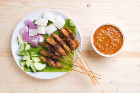 Overhead view delicious chicken satay on wooden dining table, one of famous Malaysian local dishes.