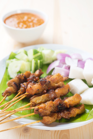Delicious chicken satay on wooden dining table, one of famous Malaysian local dishes. photo