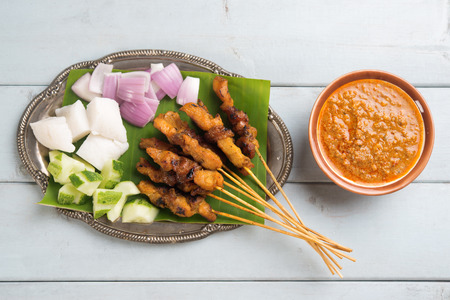 Fresh chicken satay on wooden dining table, one of famous Malaysian local dishes. Stock Photo