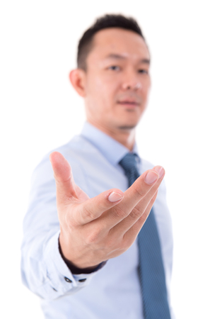 Asian business man open palm holding something, focus on palm, front view isolated over white background. photo