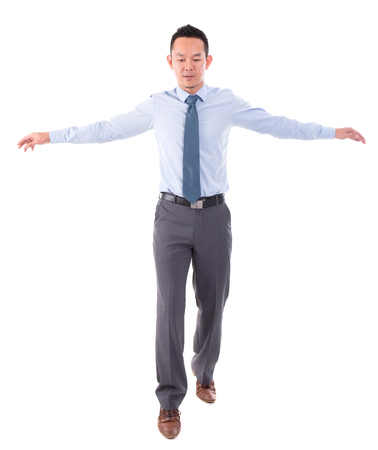 Asian business man walking balance, front view full length isolated over white background. photo