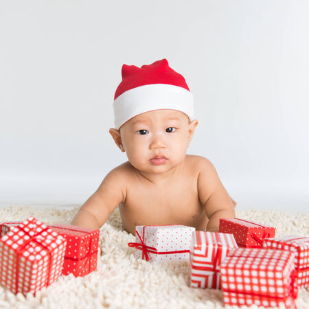 Asian santa hat baby boy with Christmas present on floor. photo
